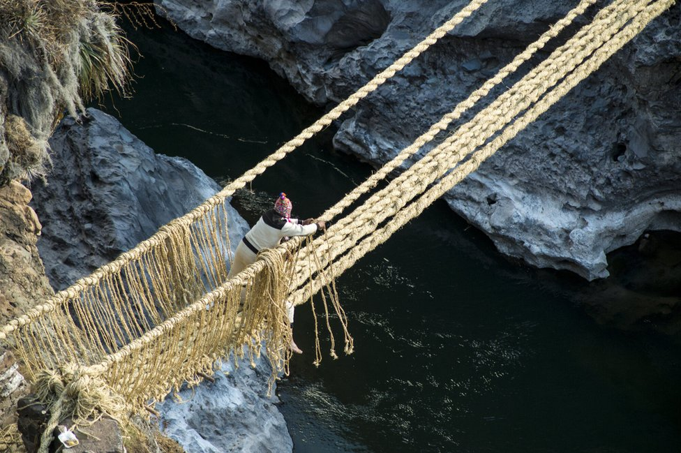 A man ties the ropes that form handrails
