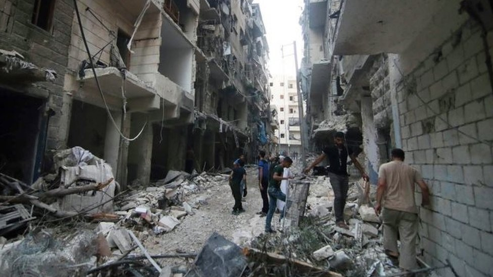Syrian citizens inspect damaged buildings after airstrikes hit Aleppo (29 July 2016)