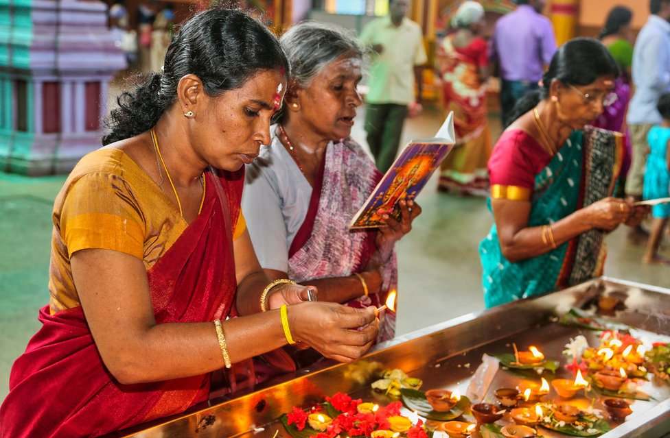 Tamil Hindu women light small lamps while offering prayers at a temple in Matale, Sri Lanka.
