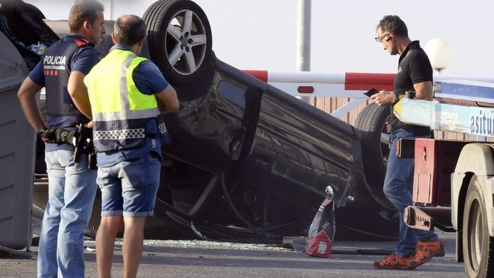 Policemen check the car involved in the attack in Cambrils