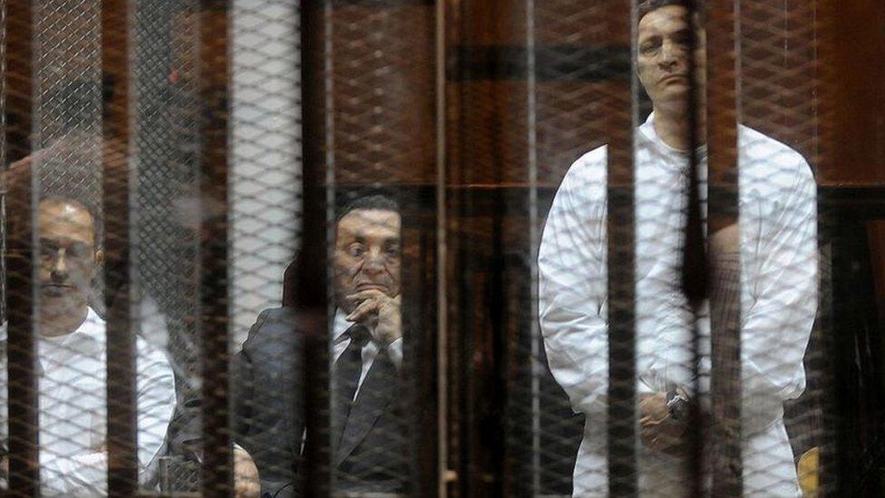 مبارك يجلس بين ابنيه علاء، على اليمين، وجمال خلال محاكمتهم في قضية فساد