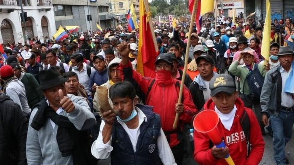 People holding flags and horns as they march through the streets