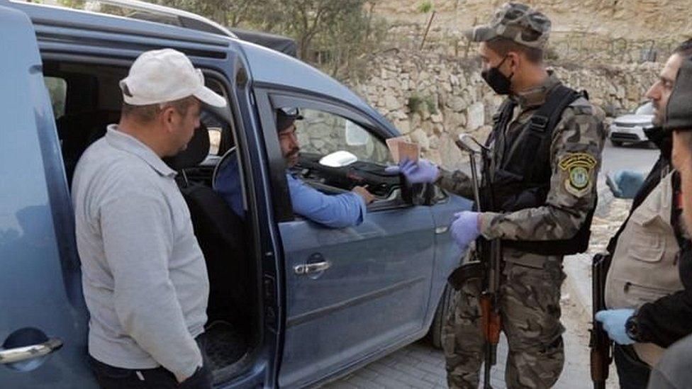 Petugas keamanan Palestina memeriksa pekerja yang ingin melintas ke Israel untuk bekerja.