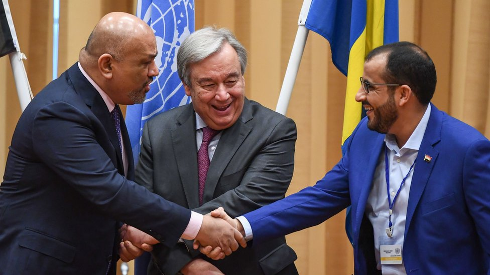 Yemen's Foreign Minister Khaled al-Yamani (L) shakes hands with Houthi representative Mohammed Abdelsalam (R) in front of UN Secretary General Antonio Guterres in Stockholm, Sweden, on 13 December 2018