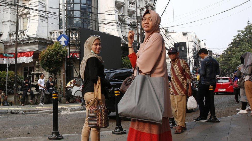 Passengers wait outside a train station in Jakarta