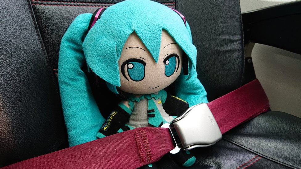 Miku, con el cinturón abrochado en su asiento del avión