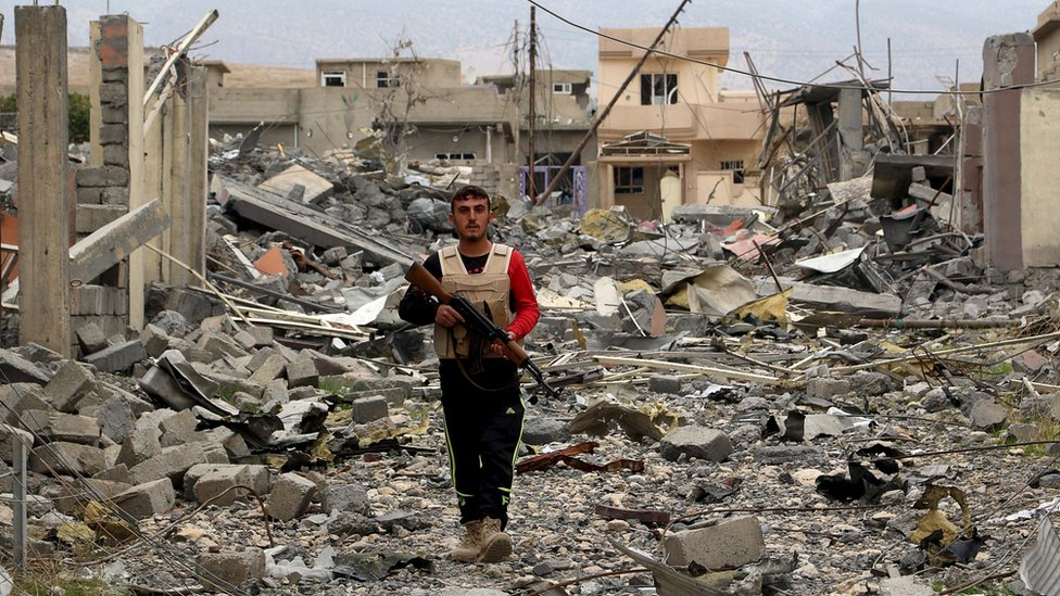 A volunteer from the Yazidi sect who joined the Kurdish peshmerga forces walks with his weapon in the town of Sinjar, Iraq, on 16 November 2015
