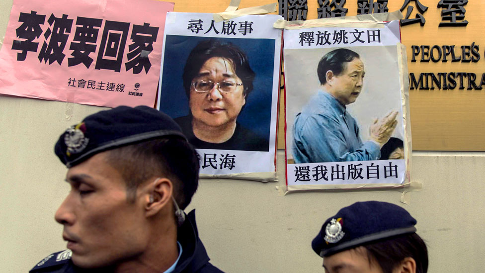This file picture taken on January 3, 2016 shows police walking past missing person notices of Gui Minhai