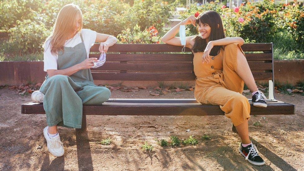 Duas meninas sentadas em um banco de parque, segurando máscaras nas mãos e praticando distanciamento social
