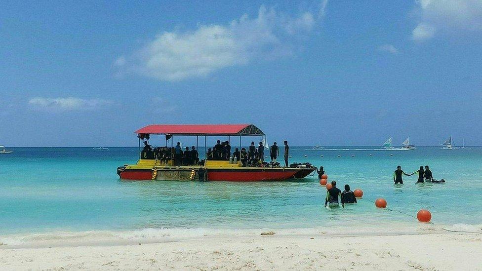 Tourists visit the beach on Boracay Island, Aklan province, on April 6, 2018