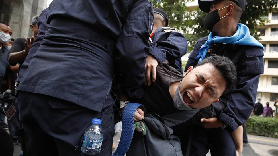 A pro-democracy protester reacts as he is being detained by police officers during a rally against the state of emergency at Ratchaprasong district in Bangkok, Thailand, 15 October 2020.