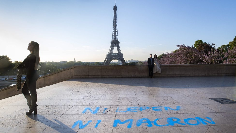 """People pose for pictures in front of the Eiffel Tower at the Trocadero plaza, where a graffiti on the ground, referring to the second round of the presidential election in France, reads """"Neither Le Pen, nor Macron"""""""