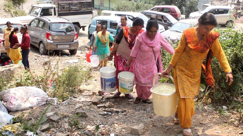 Women carrying buckets of water in Shimla