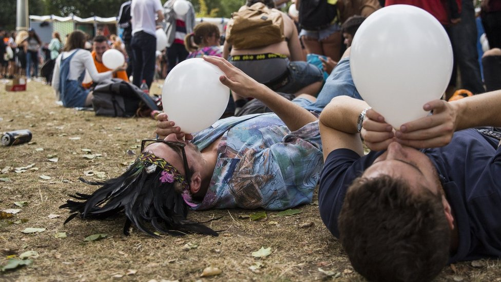 Revellers inhale nitrous oxide from balloons