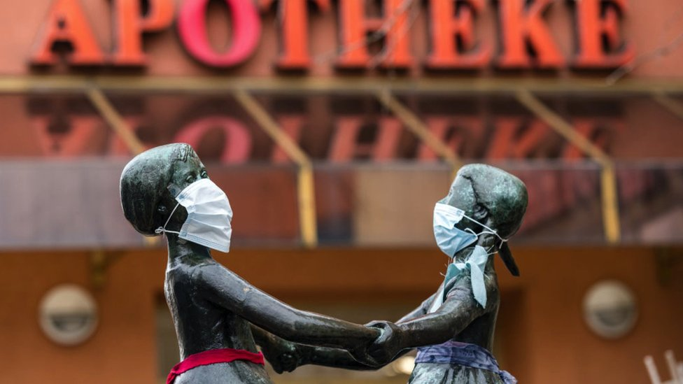 A street sceen in Germany - a statue of two children playing in front of a pharmacy, the statues have been dressed with face masks