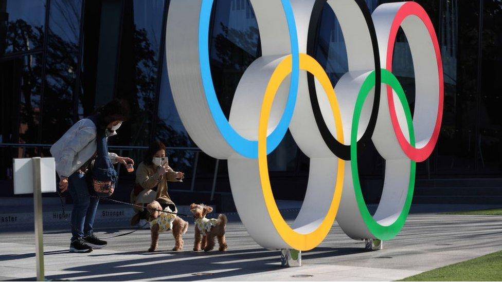 Pessoas interagem em um banco público atrás do símbolo da Olimpíada