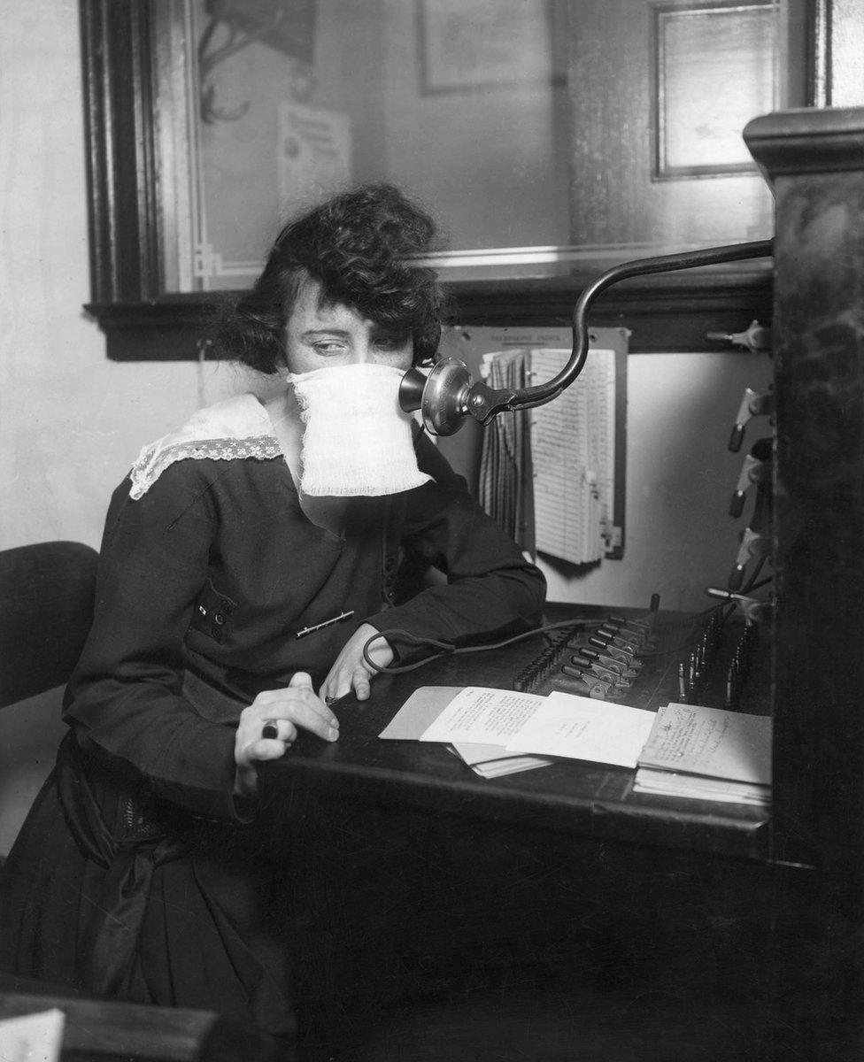 Koruyucu maske kullanan telefon operatörü