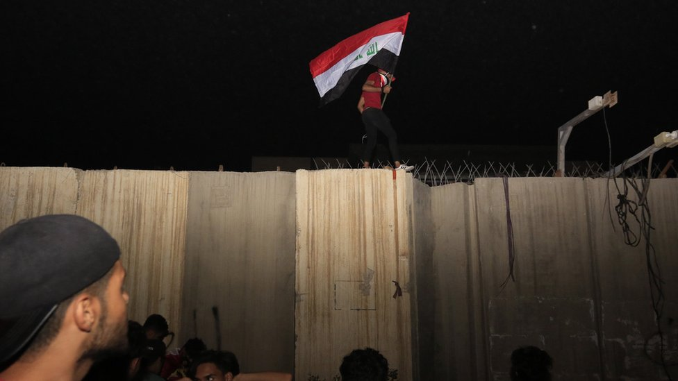 Iraqi protester carries an Iraqi flag on the wall around the Iranian consulate in the holy city of Karbala (3 November 2019)