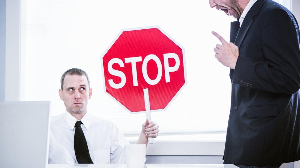 """Trabajador con una señal de """"Stop"""" ante un jefe abusivo."""