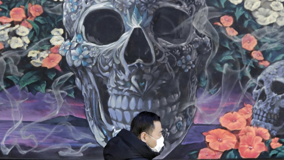 A man wears a protective face mask as he walks in front of a mural of skulls and flowers in New York