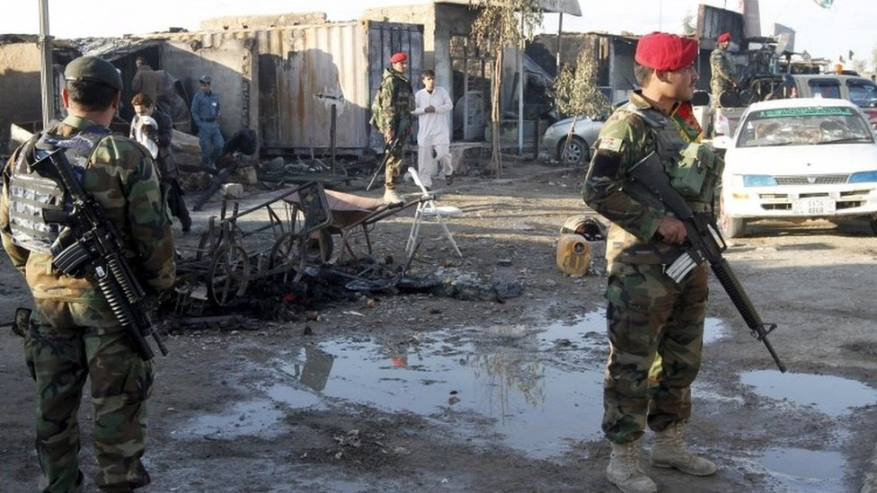 Afghan National Army (ANA) soldiers stand guard in front of a shop burned during the Taliban attack on Kandahar Airport (09 December 2015)