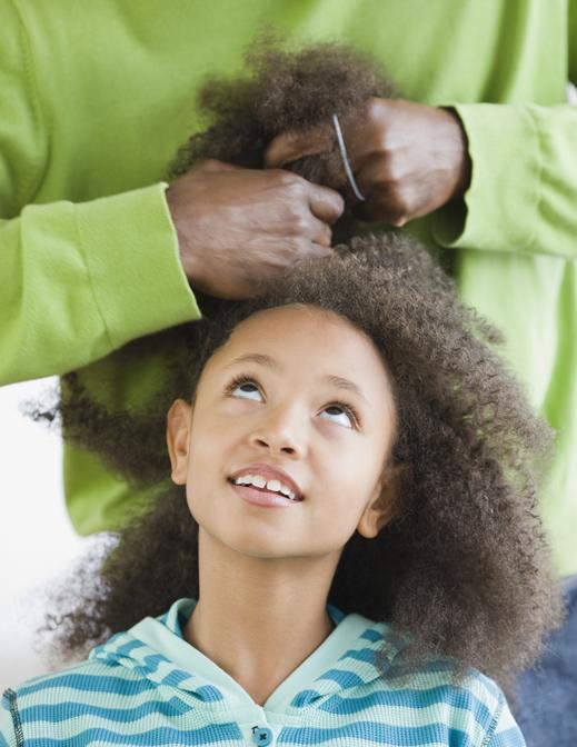 Homem penteando cabelo de menina negra