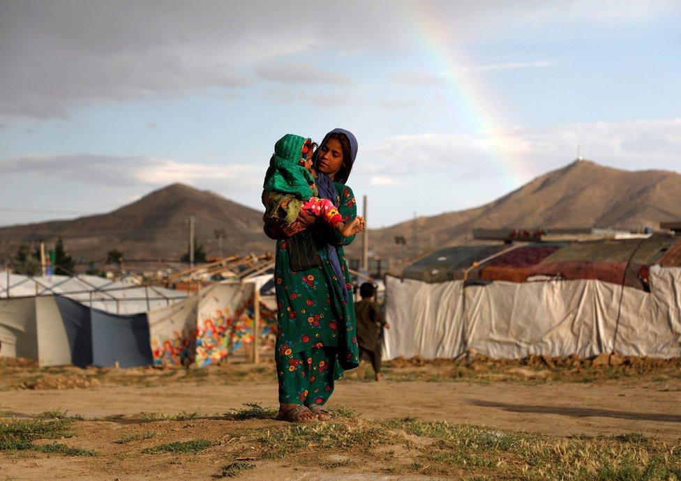 Izbeglica iz Avganistana drži dete u naručju