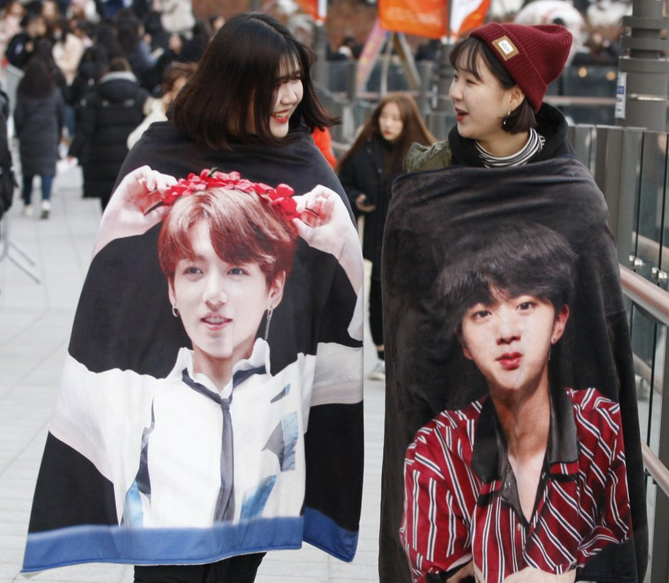 Fans of South Korean boy band BTS wearing coats of members Jungkook and Jin