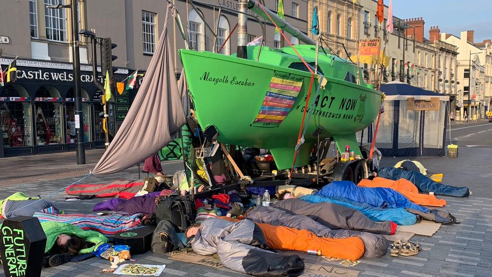 Protesters in sleeping bags surround green boat in the middle of Castle Street