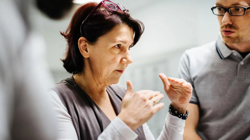 Una mujer explica algo con las manos