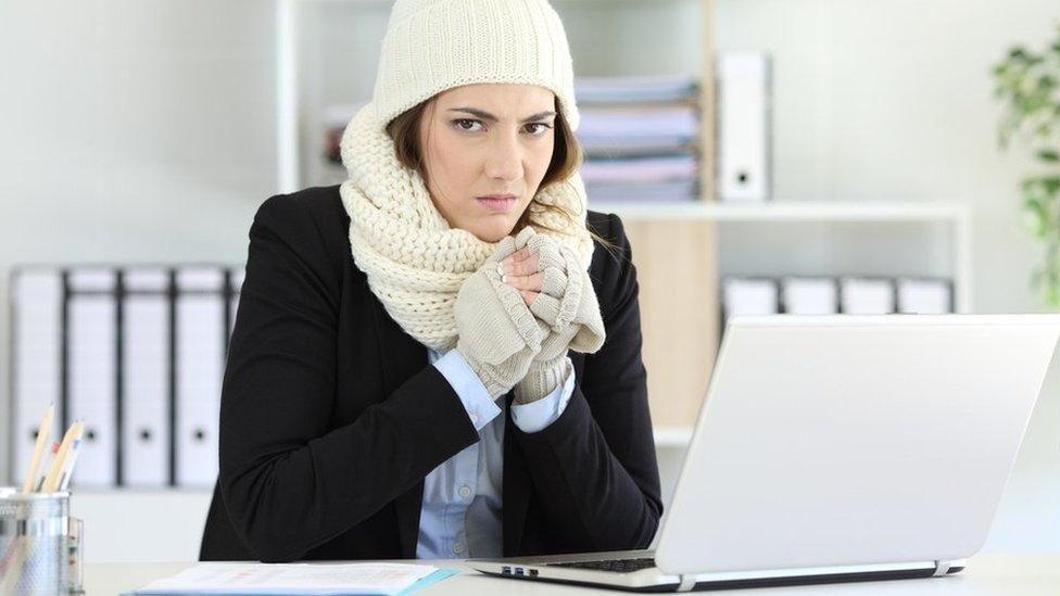 Mujer con con guantes, bufanda y gorro en la oficina.