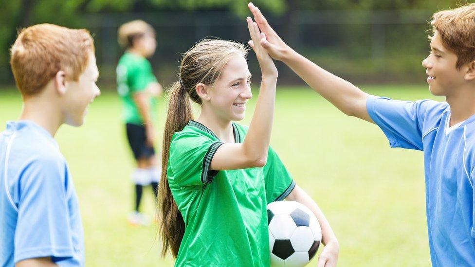 Dečaci i devojčice igraju fudbal