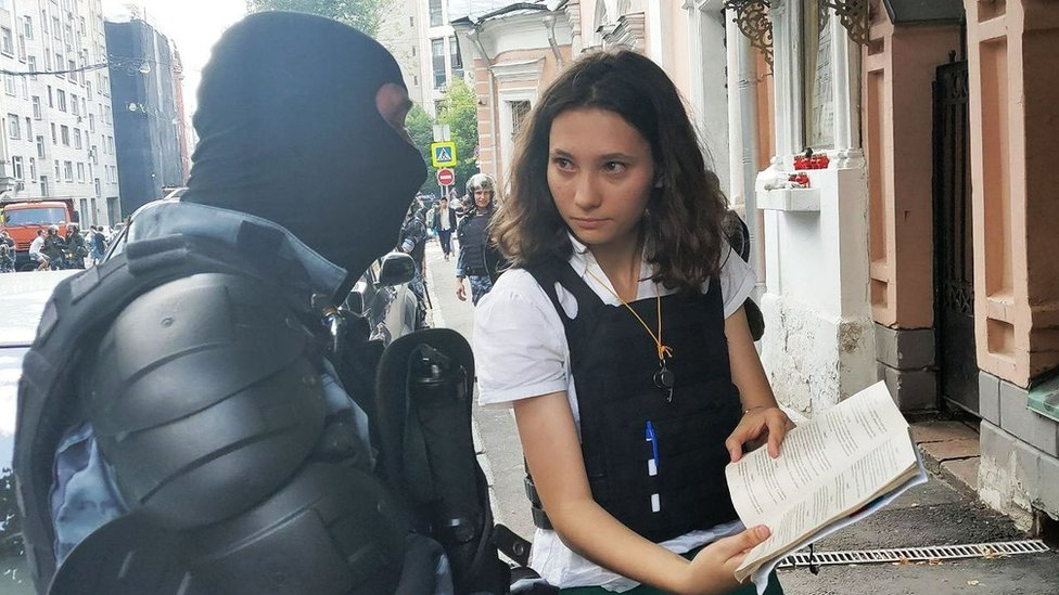 Olga showing constitution to a policeman