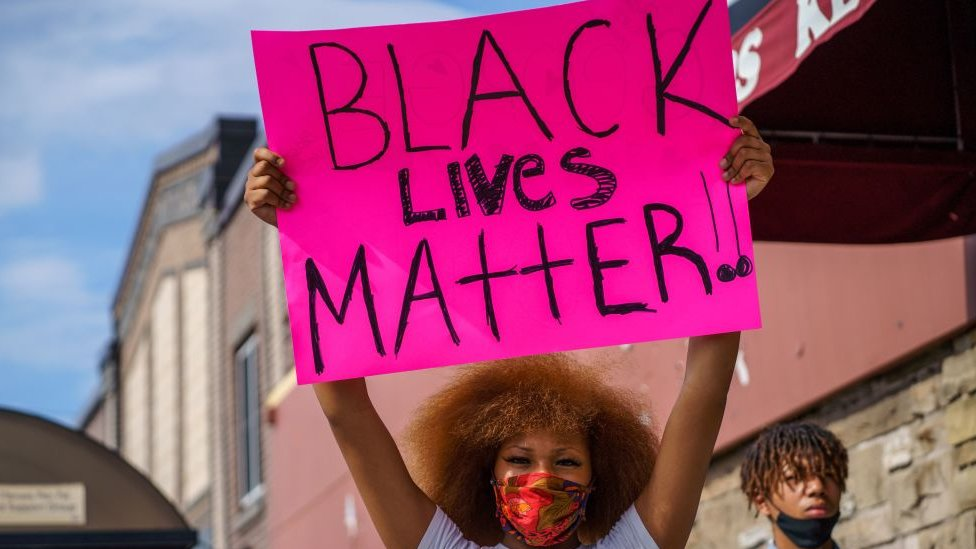 Seorang perempuan memegang spanduk Black Lives Matter