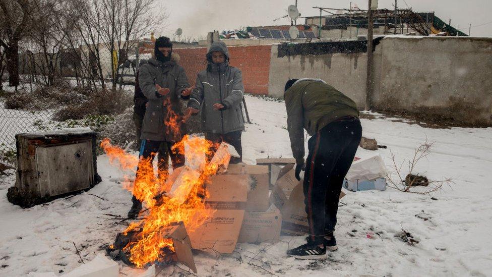 Personas en torno a una hoguera en Cañada Real, en las afueras de Madrid