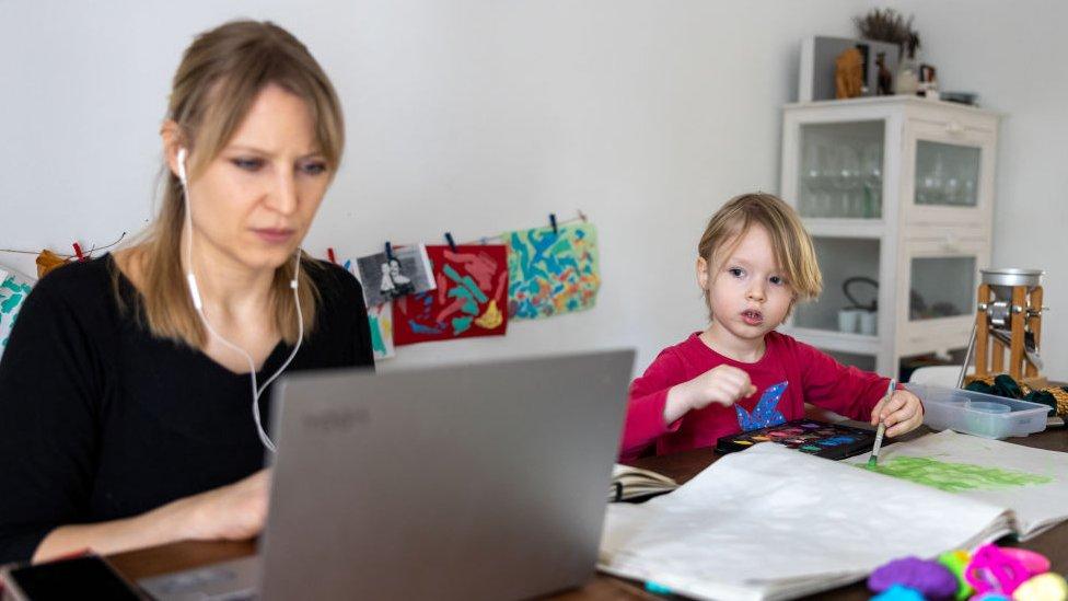 Mujer trabajando con su hijo al lado.