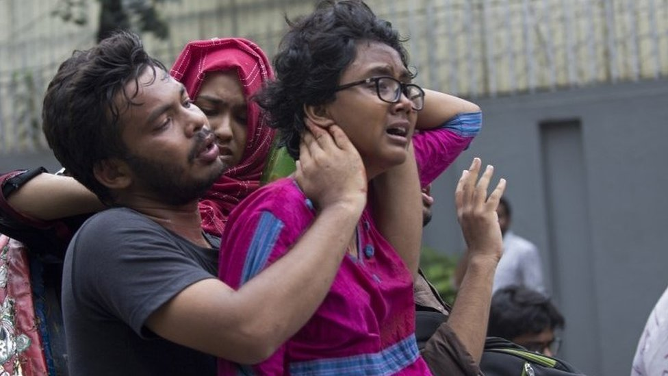People assist an injured student as Dhaka University