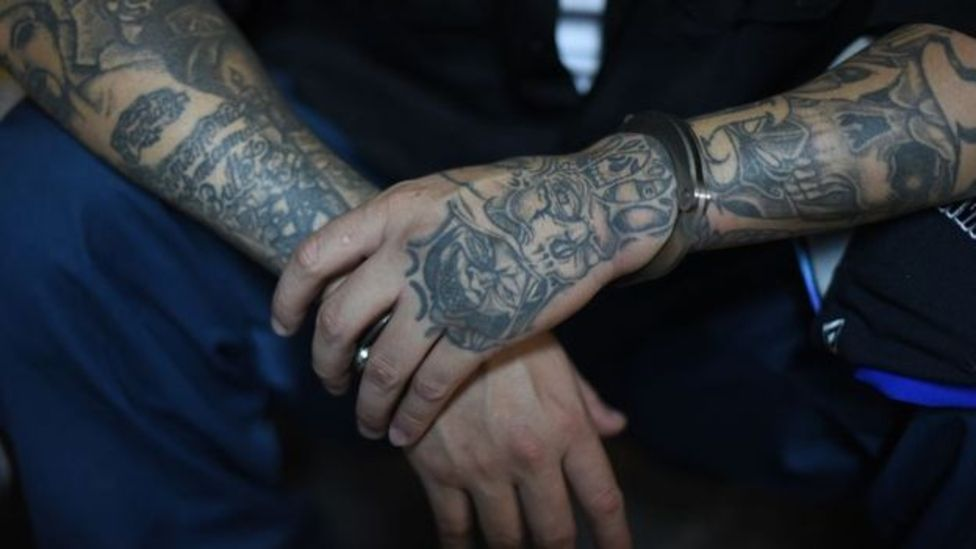 Brazos de un pandillero llenos de tatuajes.