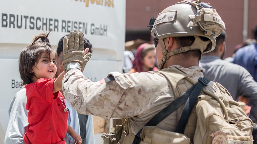在阿富汗喀布爾國際機場撤離期間,一名美國海軍陸戰隊員與一個小孩擊掌的瞬間