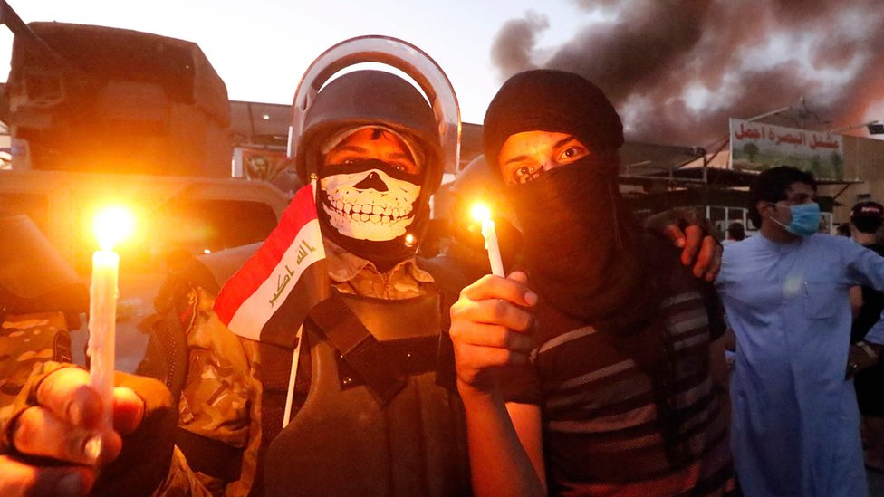 Protesters hold candles near a government building in Iraq's Basra, 6 September 2018