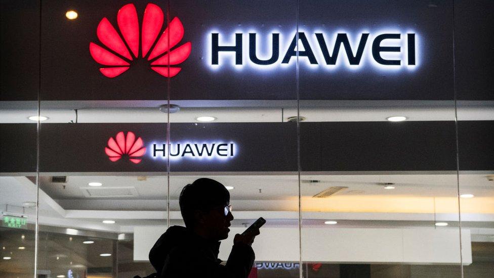 Un hombre habla por un teléfono frente a una tienda Huawei.