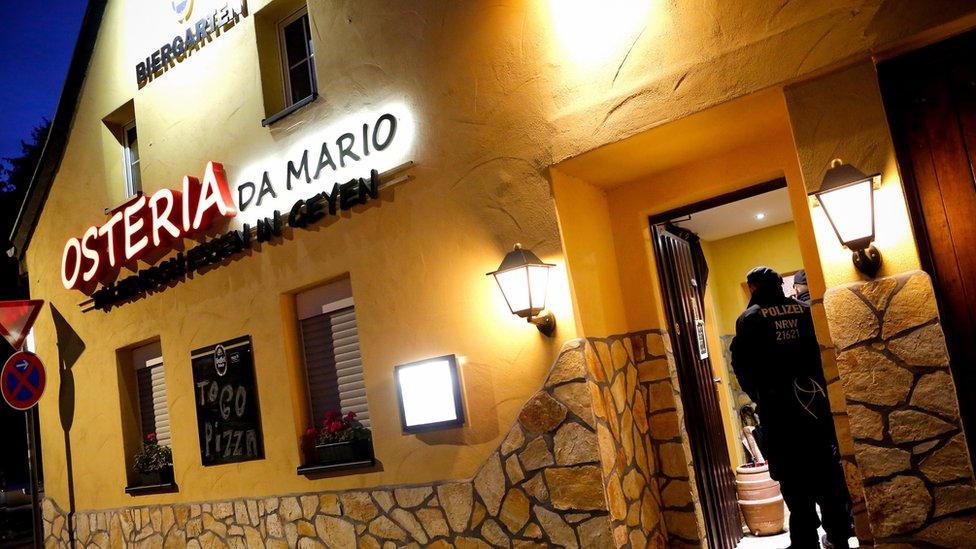 Znak na žutoj kući kaže da je u pitanju restoran Osterija Da Mario - ali dvojica policajaca čuvaju otvorena vrata na ovoj fotografiji