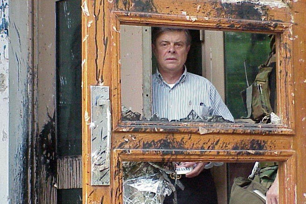 Američki ambasador Džejms Saser gleda kroz razbijena vrata američke ambasade u Pekingu