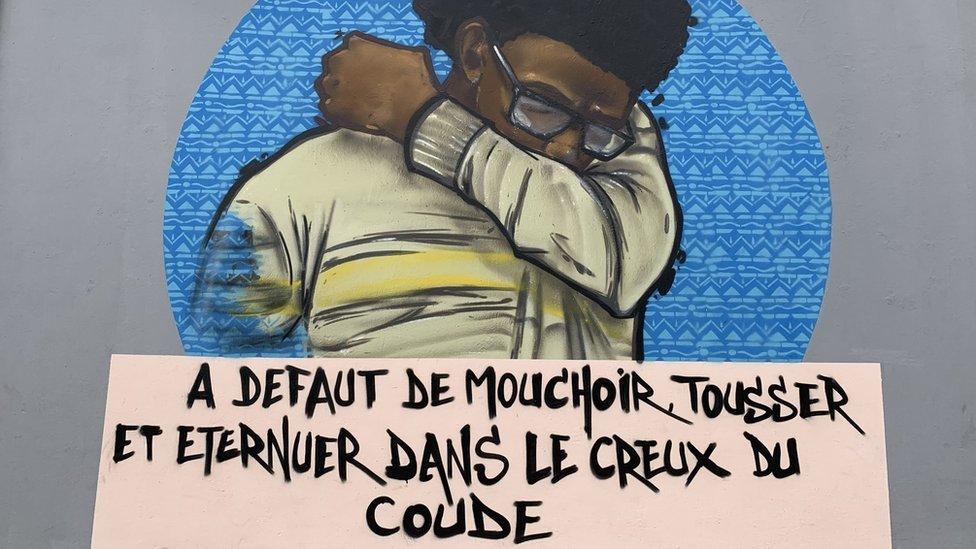Mural en Dakar de un hombre tosiendo en su codo.