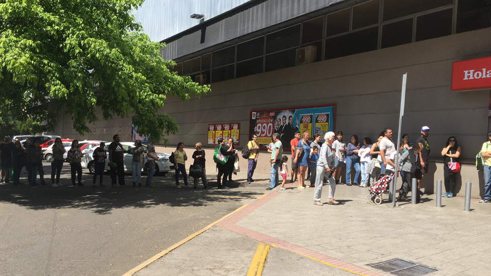 People queue in Santiago