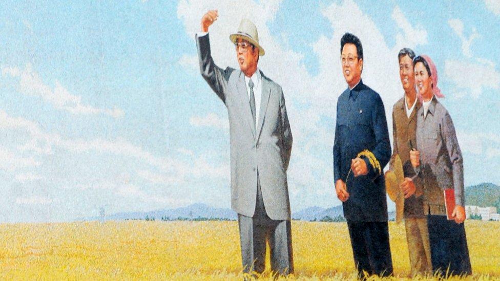 A propaganda poster showing the former North Korean leader Kim Il-Sung (L) and his son current leader Kim Jong-Il (M)