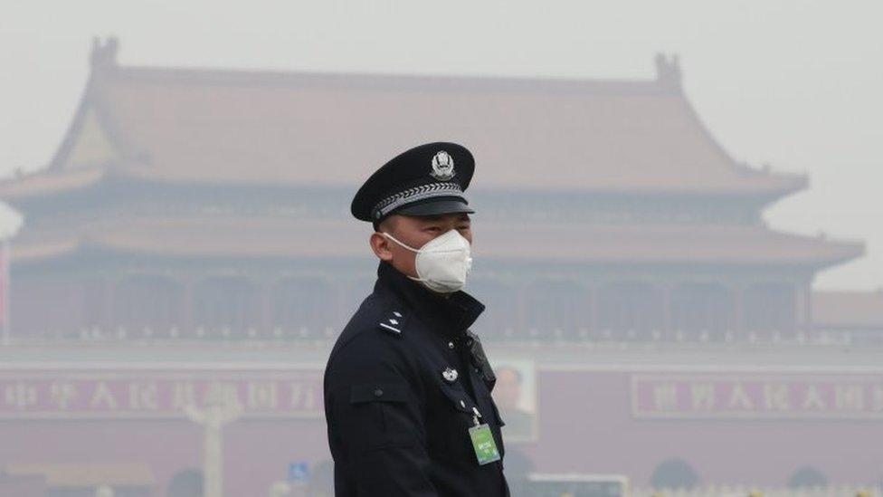 Un policía con una mascarilla en un brumoso día en Pekín