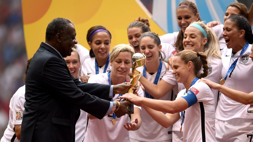 Fifa Senior Vice President Issa Hayatou of Africa hands the Wold Cup Trophy to US women's football team as they celebrate winning the Fifa Women's World Cup Canada 2015 5-2 against Japan at BC Place Stadium on 5 July 2015 in Vancouver, Canada.