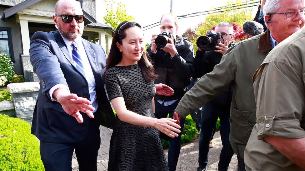 Meng Wanzhou is escorted b y security as she leaves her home on May 2019 in Vancouver