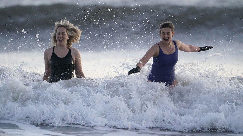 """في خليج """"كينغ إدوارد"""" بالقرب من بلدة تاين ماوث الساحلية في إنجلترا، السباحون يدخلون مياه بحر الشمال المتجمد في ليلة رأس السنة الجديدة."""